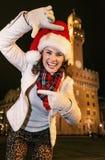 Kvinna i julhatt nära Palazzo Vecchio som inramar med händer Royaltyfri Fotografi