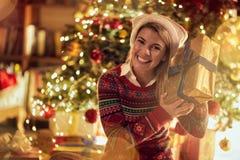 Kvinna i jultomten hatt med julklappar royaltyfria bilder