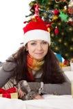 Kvinna i jultomten hatt och pälstumvanten som ligger under julgranen Royaltyfria Bilder