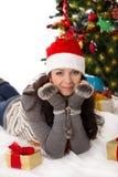 Kvinna i jultomten hatt och pälstumvanten som ligger under julgranen Arkivbild