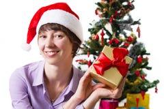 Kvinna i jultomtenhatt med gåva under det Cristmas trädet Arkivfoton