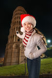 Kvinna i jultomtenhatten som tar fotoet av det lutande tornet av Pisa, Italien Arkivfoto