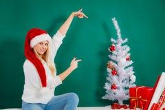 Kvinna i jultomtenhattsammanträde på att koppla av för soffa Arkivbild