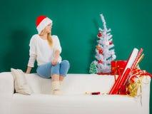 Kvinna i jultomtenhattsammanträde på att koppla av för soffa Fotografering för Bildbyråer
