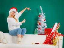 Kvinna i jultomtenhattsammanträde på att koppla av för soffa Royaltyfri Fotografi