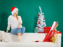 Kvinna i jultomtenhattsammanträde på att koppla av för soffa Arkivfoto