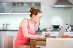 Kvinna i kök med bärbara datorn och ett exponeringsglas av vin Royaltyfri Bild