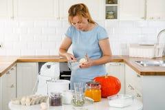 Kvinna i kök med pumpor Arkivbild