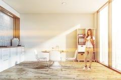 Kvinna i kök med tabellen och bokhyllan royaltyfria bilder