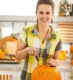Kvinna i kök som snider den stora orange pumpaStålar-NOLLA-lyktan Arkivbilder