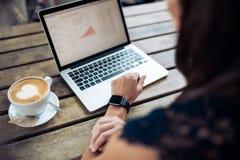 Kvinna i kafé genom att använda senast teknologiapparater royaltyfria foton