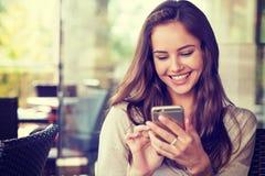 Kvinna i kafé som dricker kaffe och använder hennes mobiltelefon royaltyfri foto