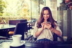 Kvinna i kafé som dricker kaffe och använder hennes mobiltelefon fotografering för bildbyråer