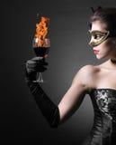 Kvinna i karnevalmaskering och en rött vin. Fotografering för Bildbyråer
