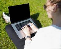 Kvinna i keyboarding för solglasögonlivsstilförfattare på bärbar datordatoren med kopieringsutrymme på skärmen royaltyfri bild