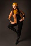 Kvinna i kläder för säsongvintervår som poserar i studio Arkivfoton