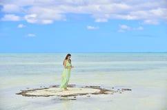 Kvinna i klänning på en bank i havet Royaltyfri Bild