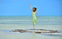 Kvinna i klänning på en bank i havet Arkivfoto