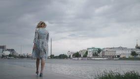 Kvinna i klänning som går på sjösida arkivfilmer