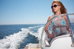 Kvinna i klänningen som kör en snabb motorbåt royaltyfria foton