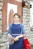 Kvinna i klänninghållpacke av blommor Royaltyfri Bild