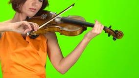 Kvinna i klänninglekarna en fiol grön skärm arkivfilmer