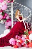 Kvinna i klänningmolnet burgundy Fotografering för Bildbyråer