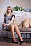 Kvinna i klänningsammanträde på soffan royaltyfri fotografi