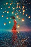 Kvinna i klänninganseende på vatten mot lyktor som svävar i en natthimmel Arkivbild