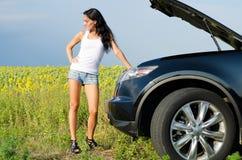 Kvinna i kortslutningar med brutet ner bilen Arkivbilder
