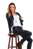 Kvinna i läderomslaget som poserar i studiobakgrund medan seate royaltyfri bild