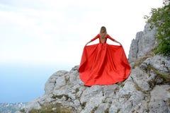 Kvinna i lång röd klänning på kanten av en klippa i bergen Maximum av detPetri berget arkivbild