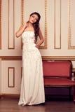 Kvinna i lång vit aftonbröllopsklänning i antik inre L Arkivbilder