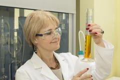 Kvinna i laboratorium som mäter cylindern Arkivfoton