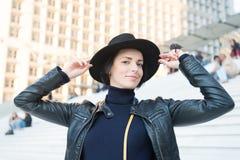 Kvinna i leende för svart hatt på trappa i paris, Frankrike, mode Sinnlig kvinna med brunetthår, frisyr Mode tillbehör, vagel Royaltyfri Foto