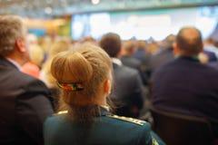 Kvinna i likformig med skuldraremmar och folk som lyssnar på konferensen Se mer i min portfölj Royaltyfria Foton