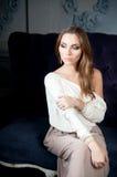 Kvinna i ljus klänning i rum, på soffan elegans Royaltyfri Foto