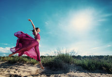 Kvinna i luftig klänningspring på stranden Arkivfoton