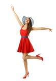 Kvinna i lyckligt gå för röd klänningstrandhatt med öppna armar, vit royaltyfria bilder