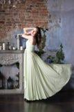 Kvinna i lyxig beige klänning Modeinre arkivbild