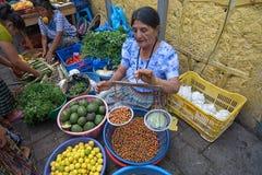 Kvinna i marknad med handtagskalan Arkivfoton