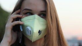 Kvinna i maskeringen som talar vid telefonen stock video