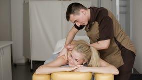 Kvinna i massage Ung attraktiv blond kvinna som ler med en massage arkivfilmer
