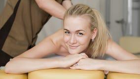 Kvinna i massage Ung attraktiv flicka som ler med en massage lager videofilmer