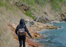Kvinna i med huva gå på kustlinjen royaltyfria bilder