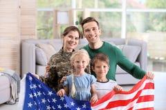 Kvinna i militär likformig med hennes familj arkivbilder