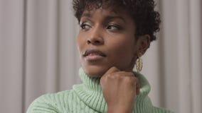 Kvinna i mintkaramelltröja i studio med grå gardinbakgrund, 90-taloffisestil lager videofilmer
