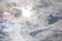 Kvinna i moln Arkivbild