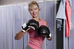 Kvinna i omklädningsrum med låsbara skåp i idrottshallen Arkivfoton