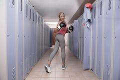Kvinna i omklädningsrum med låsbara skåp i idrottshallen Royaltyfria Bilder